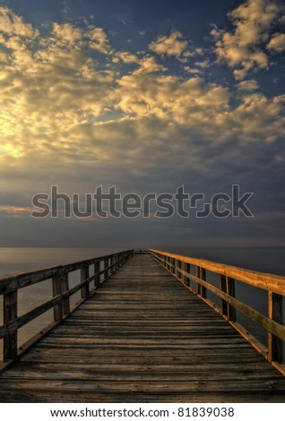 Long wooden fishing pier at Port Mahon, Delaware extending over the Delaware Bay. - stock photo