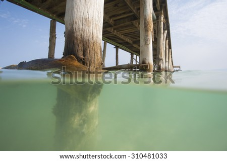 Long wooden jetty in the sea from a tropical island lagoon on beach showing underwater support - stock photo