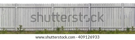 Long wooden rural fence from vertical gray pine boards. Young fir trees are planted on a lawn before a fence. Isolated on top - stock photo