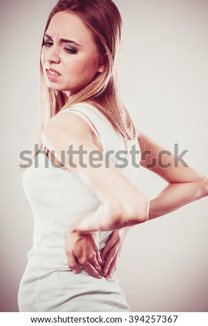 Long working hours and health. Young female with backache. Woman with back pain on gray - stock photo