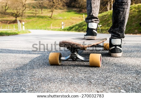 Longboard and feet of young boy in sneakers on a road - stock photo
