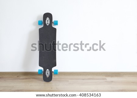 Longboard standing at the wall. - stock photo