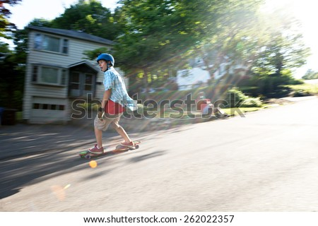 Longboarder skating on an urban road with lens flare while being filmed by another man. Slight motion blur from panning technique to capture movement. - stock photo
