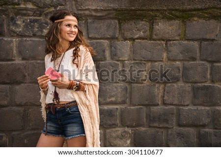 Longhaired hippy-looking young lady in jeans shorts, knitted shawl and white blouse standing near stone wall in old town and holding cell phone - stock photo