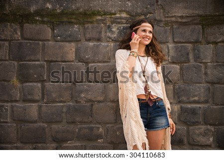 Longhaired hippy-looking young lady in jeans shorts, knitted shawl and white blouse standing near stone wall in old town and talking cell phone - stock photo