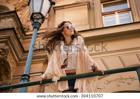 Longhaired hippy young lady in jeans shorts, knitted shawl and white blouse with sunglasses stands near streetlight in old town looking at skies - stock photo