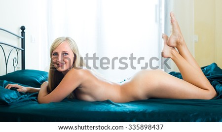 Longhaired nude girl lying on bed in seductive pose