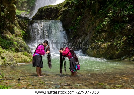 LONGJI, CHINA - MAY 24, 2010: Unidentified women wash their hair at a stream in the village. Red Yao ethnic minority women here regard keeping long hair as a sign of beauty.. - stock photo