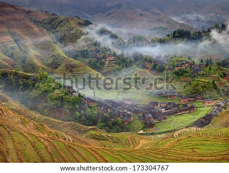 Longsheng, near Guilin, Guangxi Province, China. Spring landscape with village and rice terraces, mountain rural China. Peasant village in mountainous region of China agricultural, rural landscape. - stock photo