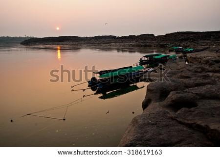 Longtail boat, Berth at sand Sam Pan Bok Grand Canyon in Maekhong river, Northeast of Thailand. - stock photo
