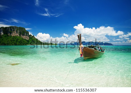 Longtail boat in the beautiful sea over clear sky - stock photo