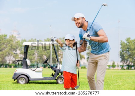 Look at that! Cheerful young man embracing his son and looking away while standing on the golf course - stock photo