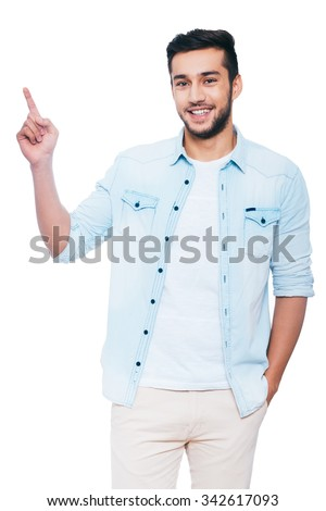 Look at that! Confident young Indian man pointing copy space and smiling while standing against white background - stock photo
