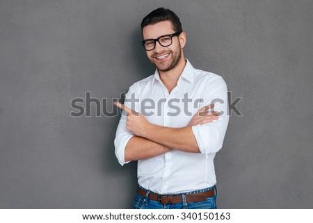 Look at that! Handsome young man pointing away and smiling while standing against grey background  - stock photo