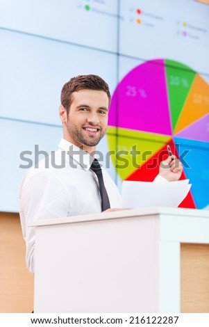 Look at the diagram! Cheerful young man in formalwear standing at the tribune and pointing projection screen while making a presentation  - stock photo