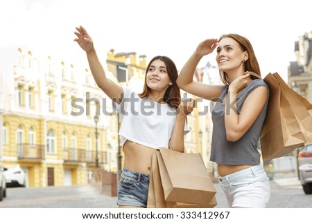 Look at this! Beautiful brunette smiling and pointing at the shop to her friend, both carrying shopping bags - stock photo