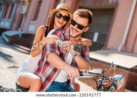 Look at this photo! Beautiful young couple sitting on scooter together while happy woman showing something at her mobile phone - stock photo