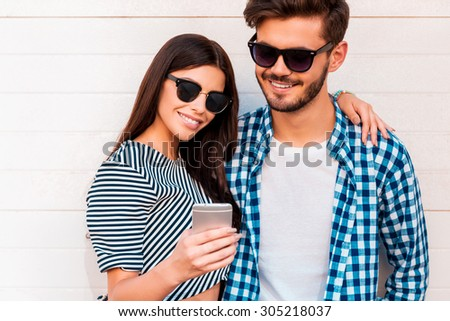 Look at this photo! Beautiful young woman showing something on her mobile phone to her boyfriend while standing outdoors together  - stock photo