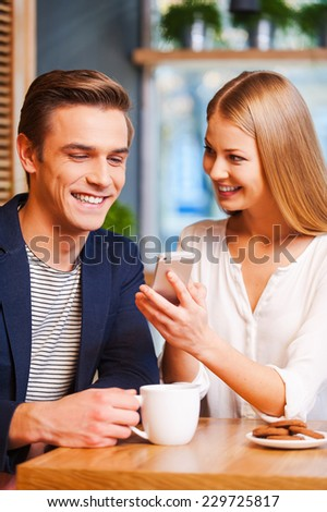 Look at this photo! Beautiful young woman showing something on mobile phone to her boyfriend while enjoying coffee in cafe together  - stock photo