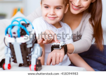 Look how it works.  Cheerful delighted smiling mother playing with robot while sitting  on the couch with her little daughter - stock photo