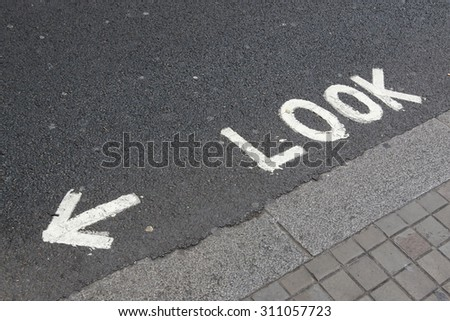 Look left before crossing, sign on the asphalt road - stock photo