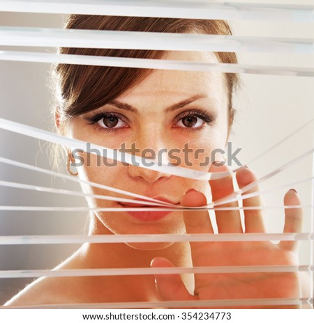 look of woman who observes through blinds - stock photo