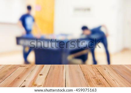 Look out from the table, blur image of young mans playing billiard as background. - stock photo