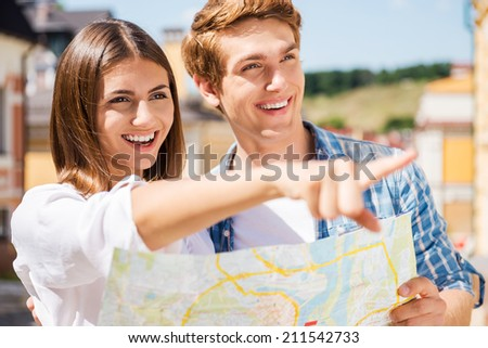 Look over there! Happy young tourist couple holding map while woman pointing away and smiling - stock photo