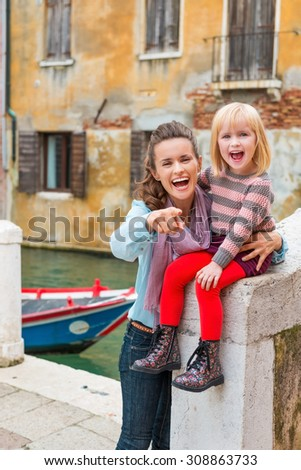 Look, there's Daddy! Let's give him a big smile! A mother happily holds her laughing daughter as she sits near the water on a stone bridge in Venice. The daughter is proud of her red tights! - stock photo
