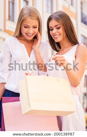 Look what I got! Beautiful young woman showing her friend what she got in her shopping bag while both standing outdoors  - stock photo