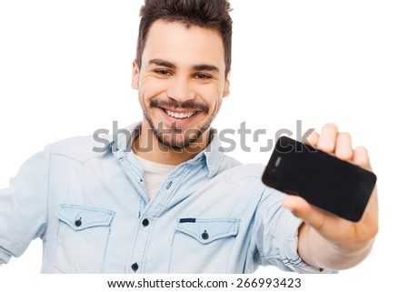 Look what I got! Cheerful young man showing mobile phone and smiling while standing against white background - stock photo