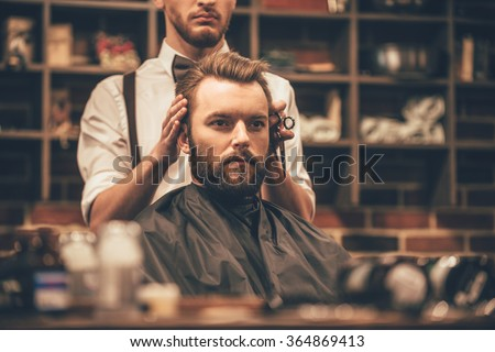 Looking amazing. Close-up of hairdresser checking symmetry of haircut of his client at barbershop - stock photo