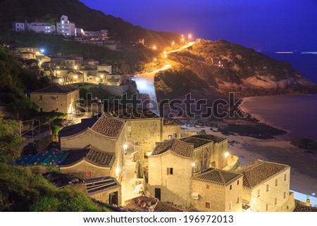 Looking at buildings and a road from a hill beside them. - stock photo