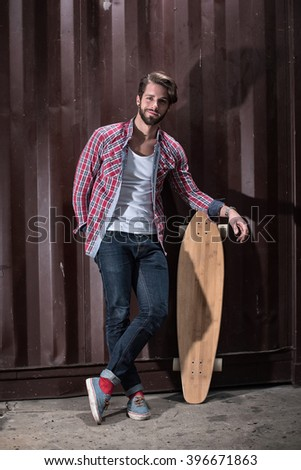 Looking at camera, a young trendy man leaning against a wall with his stakeboard. he wears casual clothes - stock photo
