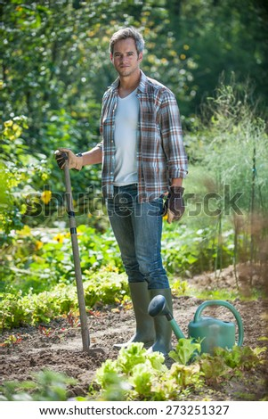 looking at camera, portrait of a man with a spade doing gardening - stock photo