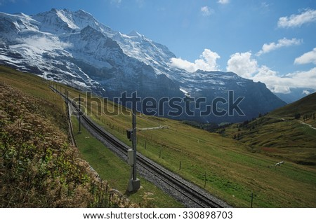 Looking at the railway from Kleine Scheidegg towards the Jungfraujoch (Berner Oberland, Switzerland). The Kleine Scheidegg is a mountain pass (2,061 metre), below and between the Eiger and Laubhorn. - stock photo