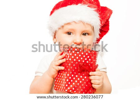 Looking baby in red Christmas hat with gift box - stock photo