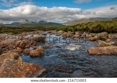 Looking down a highland stream towards the Beinn Dearg group of hills to the east of the A835 near Ullapool, Scotland - stock photo