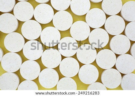 Looking down at a group of Vitamin C pills on a yellow background. - stock photo