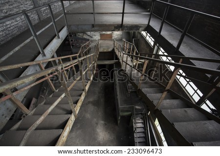 looking down at rusty stairs in an abandoned factory - stock photo