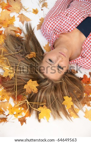 looking down at teenager laying in the leaves - stock photo
