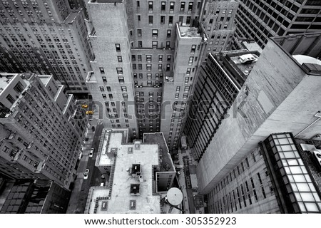 Looking down at yellow cabs in the streets of New York, USA, as small colorful dots in black and white composition of tall skycrapers - stock photo