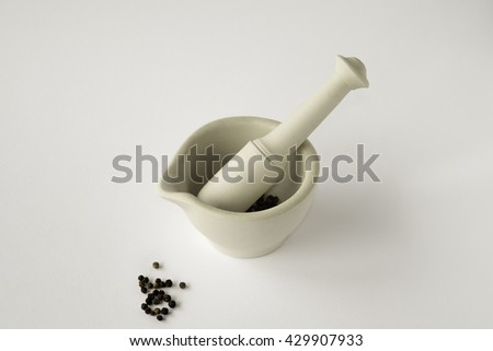 Looking down on ceramic mortar and pestle with black peppercorns on white background - stock photo