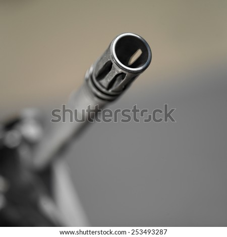 Looking down the barrel of a non identifiable machine gun, shallow depth of field square shot - stock photo