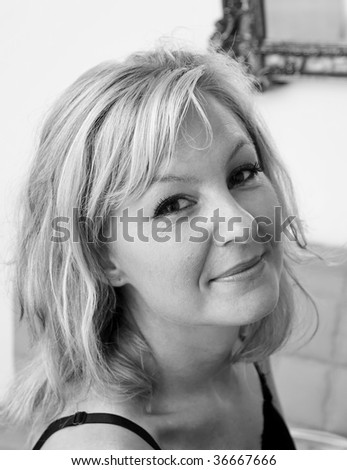 looking down towards a beautiful blonde woman that is looking at viewer with shoulders turned and a small smile on her lips, black and white image - stock photo