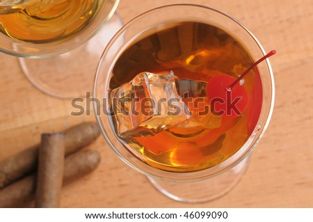 Looking down two Manhattan Cocktails in Martini Glasses with cigars on wood background horizontal format - stock photo