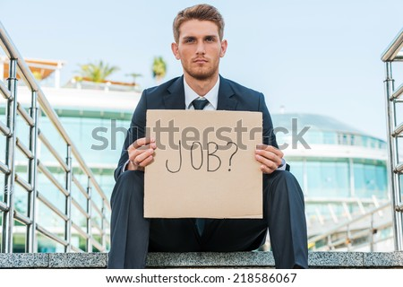 Looking for a job. Handsome young man in formalwear holding poster with job text message while sitting outdoors and with building structure in the background - stock photo