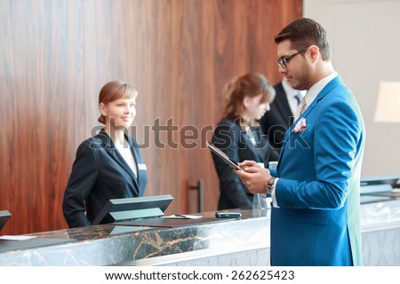 Looking for check-in information. Young handsome businessman in classical blue suit looks at his tablet device standing just in front of the hotel reception desk where young receptionists welcomes him - stock photo