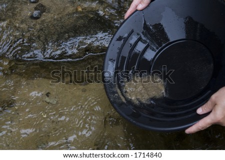 looking for gold in a small stream in northern Michigan by Mackinaw city black pan with sand and gravel in the pan - stock photo