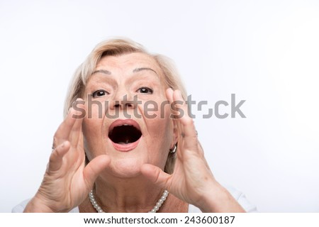 Looking for grandson. Closeup portrait of anxious elderly woman holding hands near her mouth shouting while standing against white background - stock photo